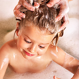 girl getting her hair washed for lice treatment